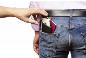 Une main attrapant un porte-monnaie dans la poche d'un homme